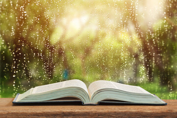 Obraz The open book which there is on a table on window glass with raindrops after summer rain - fototapety do salonu