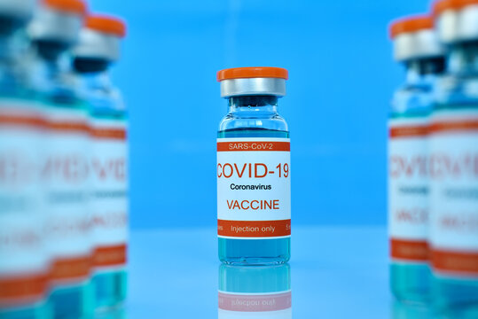 Covid-19 vaccine in bottles on blue table.