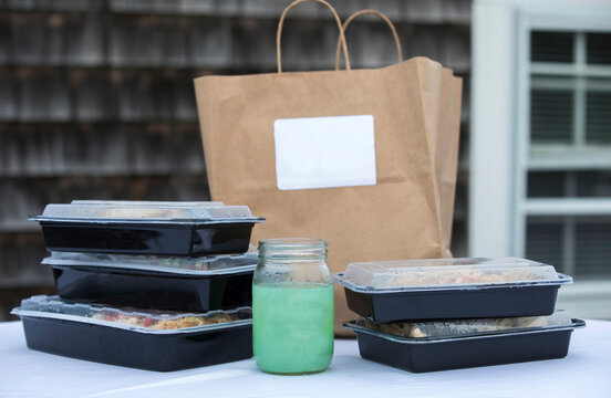 Takeout boxes piled up with brown paper bag and to-go Margarita drink