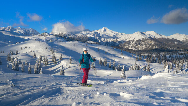 DRONE: Woman on splitboarding trip hikes along snowy hill overlooking mountains.
