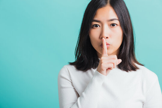 woman holding index finger on her mouth lips