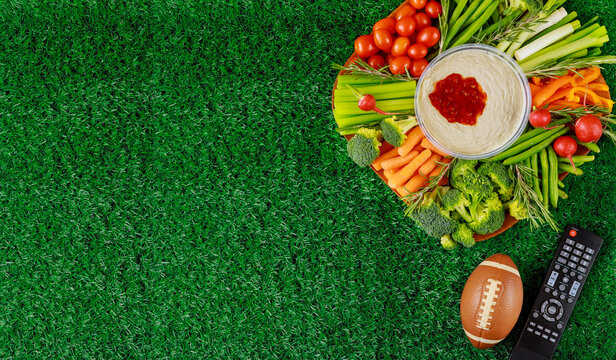 Colorful vegetable platter with football ball for american football game party.