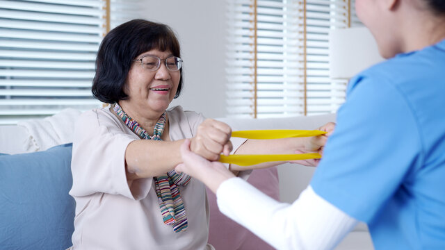 Young older senior asia citizen sit on sofa couch with in-home nursing care, assisted living, scrubs nurse doctor use resistance band exercise for senior patient in physiotherapy treatment at home.