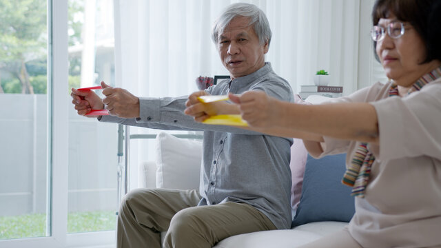 Young older senior asia citizen couple sit on sofa couch with in-home nursing care, assisted living, scrubs nurse use resistance band exercise for senior patient in physiotherapy treatment at home.
