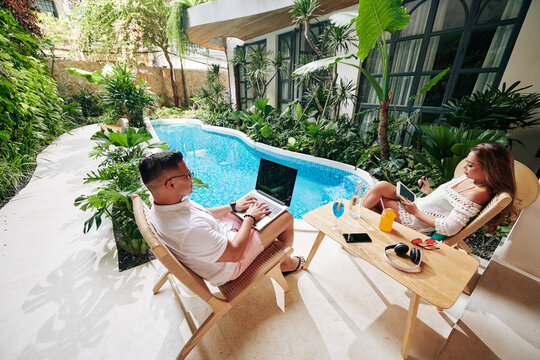 Serious married couple sitting near swimming pool in backyard, drinking cocktails and working on gadgets