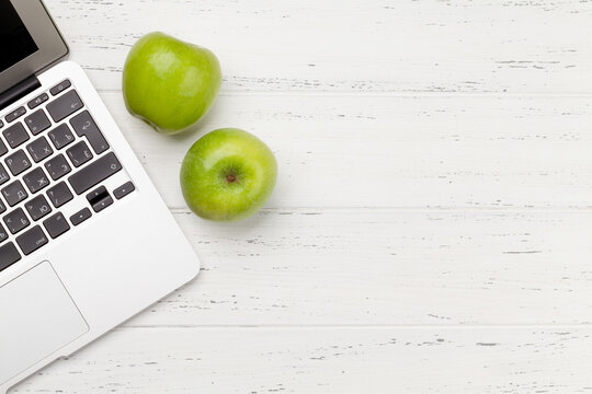Office desk with laptop and apple fruits