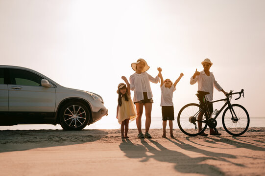 Asian family vacation holiday, Happy family happier on the beach in the evening and a car on the side. Mother, father, children on the sea at sunset.Father rides a bike.