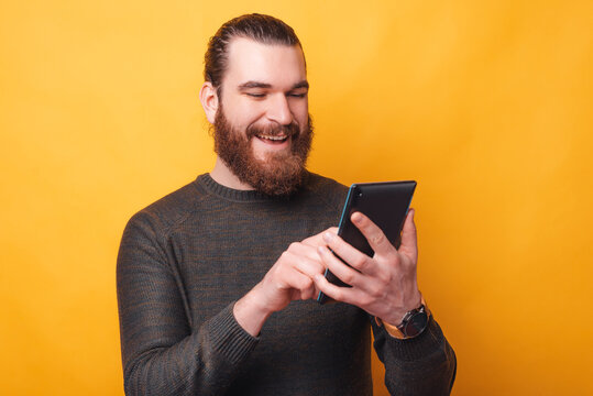 A joyful bearded man is talking with someone on his tablet being happy .