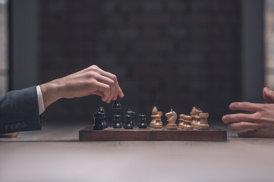 Players hand with black pawn over chessboard