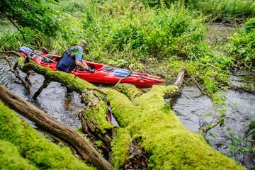 Mężczyzna pokonujący zwalone drzewo na rzece Wierzycy podczas spływu kajakowego
