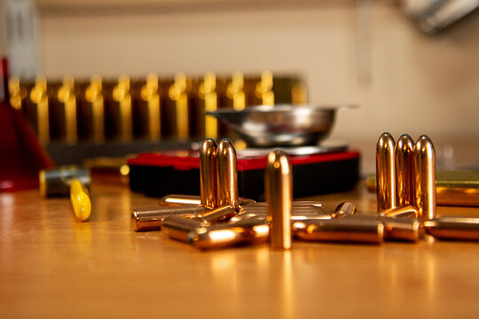 In the foreground are bullets in a shell, casings in a wooden stand on a black background, preparations for reloading cartridges, necessary accessories for reloading, soft focus
