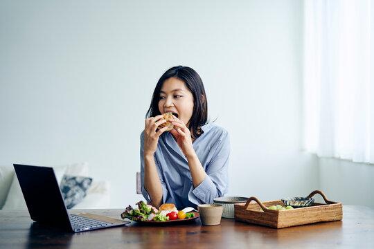 ノートパソコンを見ながら食事をする30代日本人女性