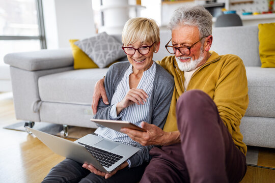 Senior couple websurfing on internet with laptop at home