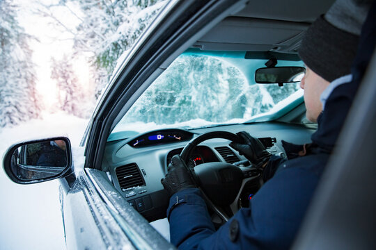 Man in warm winter clothes sitting in car. Snowy winter country road, car covered with ice, Beautiful forest under the snow.