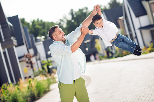 Portrait of nice cheerful careful adorable best friends daddy carrying son having fun playing outside sunny day cottage town residence