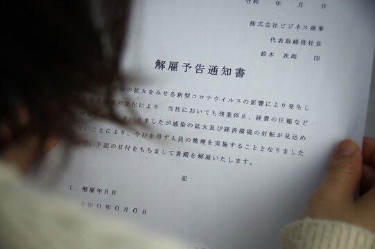 解雇予告通知書を見る女性