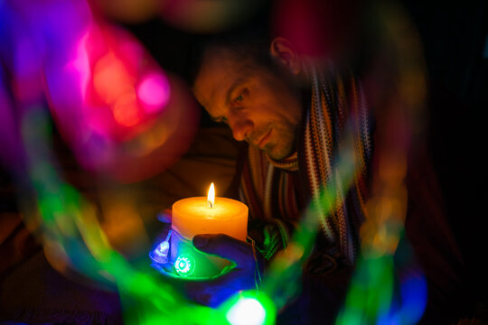 The man looks at the burning candle. Bokeh is around