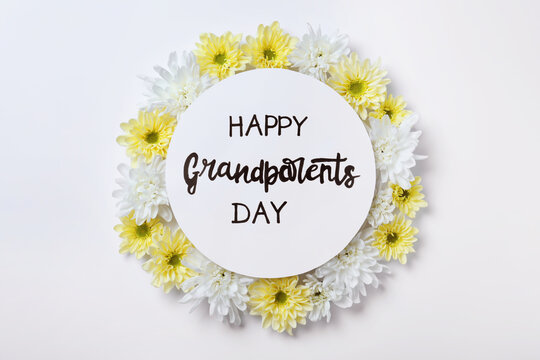 Card with phrase Happy Grandparents Day and beautiful flowers on white background, flat lay