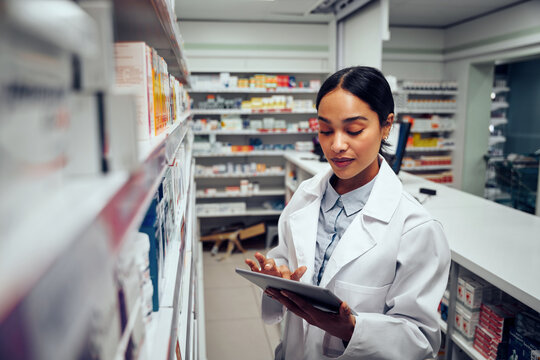 Young female pharmacist checking inventory of medicines in pharmacy using digital tablet wearing labcoat standing behind counter