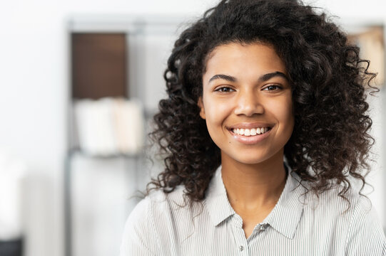 Headshot of a young elegant African American ethnic female with Afro curly hairstyle, beautiful smile and looking at the camera while standing against blurred home or office interior background