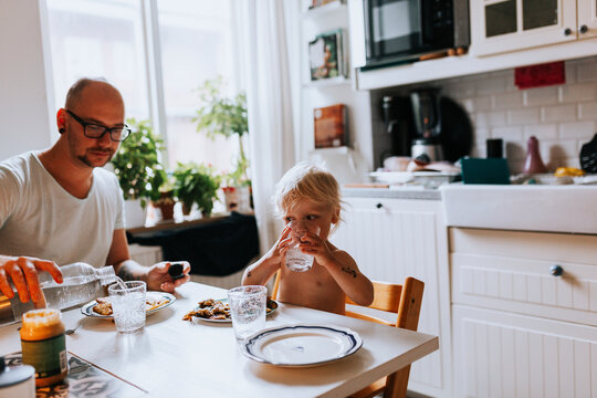 Father and toddler having meal at table