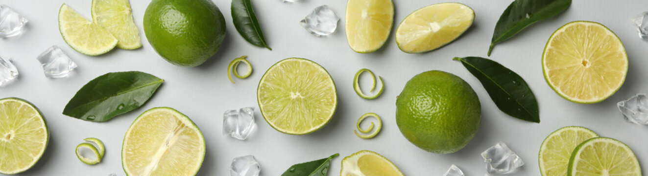 Fresh ripe limes, ice and leaves on whole background