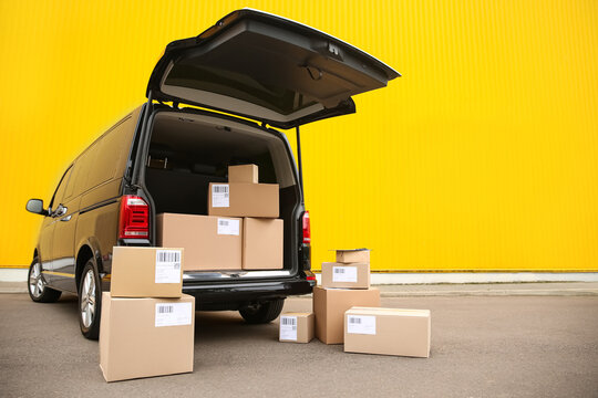 Black delivery van and many different parcels near yellow wall outdoors, space for text. Courier service