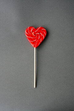 Red heart-lollipop on a gray background. Card for Valentine's day.