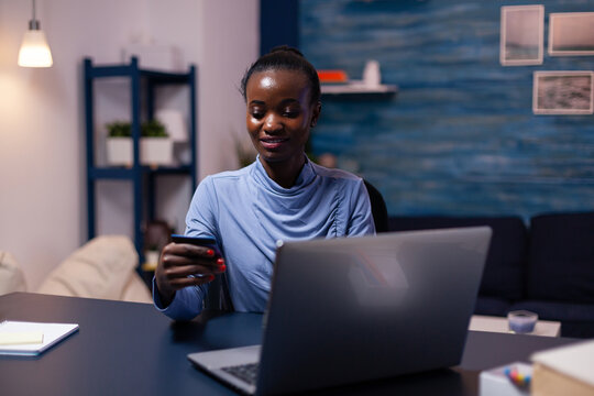 Dark skin young woman holding plastic credit card purchasing product from online shop. Employee making paymant transaction from home on digital notebook.