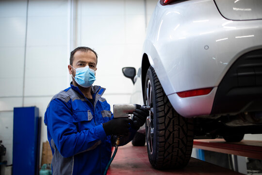 Portrait of professional car mechanic wearing face mask due to corona virus holding pneumatic screw gun and changing wheels of vehicle. Automobile service and maintenance.