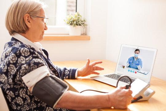Elderly senior retired woman using sphygmomanometer blood pressure monitor to measure heart rate pulse