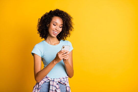 Photo of cheerful sweet dark skin wavy lady wear blue t-shirt holding modern gadget empty space isolated yellow color background
