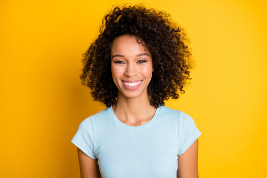Photo portrait of gorgeous afro american curly girl smiling isolated on vivid yellow colored background