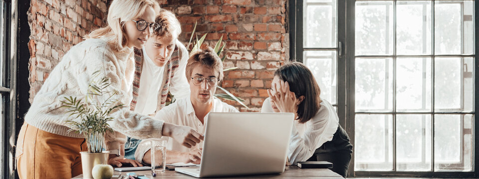 Office business teamwork concept. Group of four people working together with laptop. Wide screen