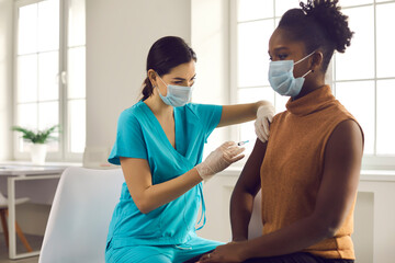 Young African American lady sitting at doctor's office and getting modern Covid 19 shot. Nurse in...