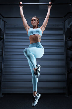 Athletic girl pulls up on the bar in the gym on a blue background. The concept of sports, fitness, aerobics, bodybuilding, stretching.