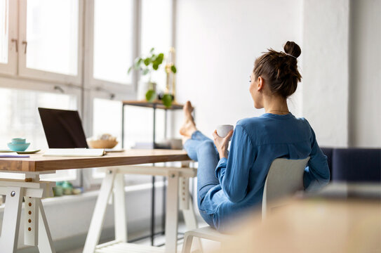 Young woman relaxing in office with her bare feet on desk