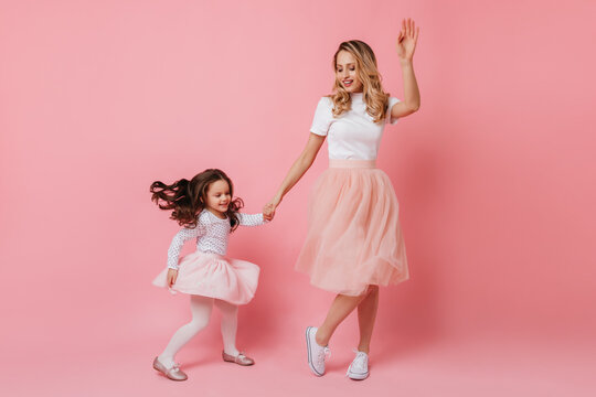 Full-length shot of cheerful adult lady and little girl in light dresses dancing on isolated background