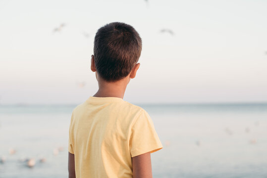 boy in a yellow shirt looks far away to horizon of sea standing alone on beach at sunset. View from back. Happy family travel. Summer vacation with child.