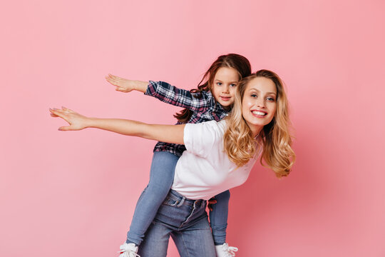 Positive lady and her daughter play, imagining themselves to be airplanes. Curly blonde woman holding baby on her back on pink background