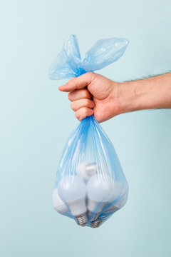 Man's hand holding energy saving light bulbs in disposable plastic garbage bag on blue background. LED bulbs. Energy saver. Eco friendly. Energy-effective lamps. Reduce and save the planet