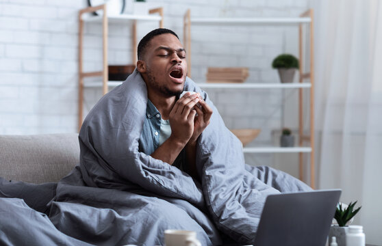 Sick African American Man Sneezing Sitting On Couch At Home