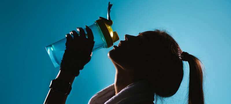 Banner, long format. Blacked-out portrait of a girl with long hair who drinking water against on blue background.