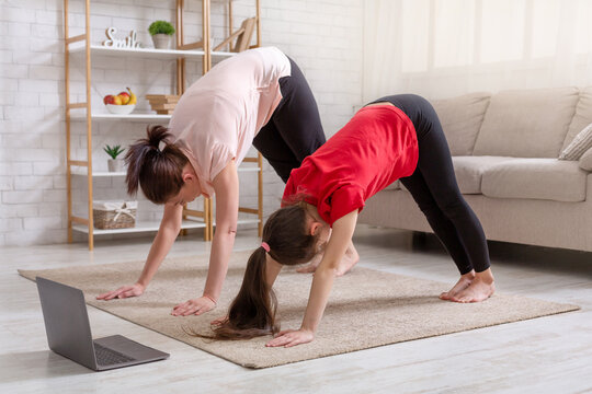 Young mother and her daughter exercising at home to online video on laptop, standing in downward facing dog yoga pose