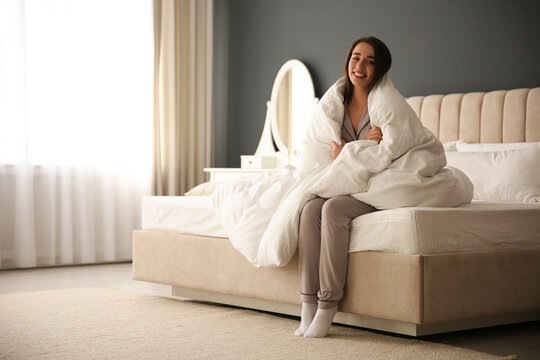 Beautiful young woman wrapped with soft blanket sitting on bed at home