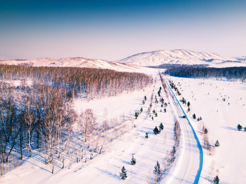 Aerial drone view of snow-covered road in countryside at sunset. Beautiful winter landscape. South Ural, Russia