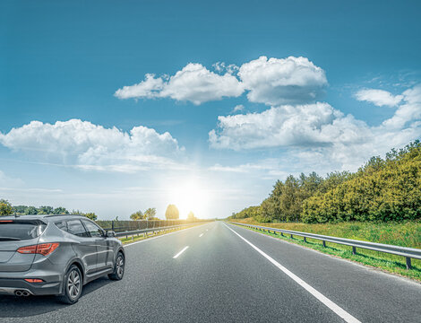 A Black car rushes along the road against the backdrop of a beautiful countryside landscape.
