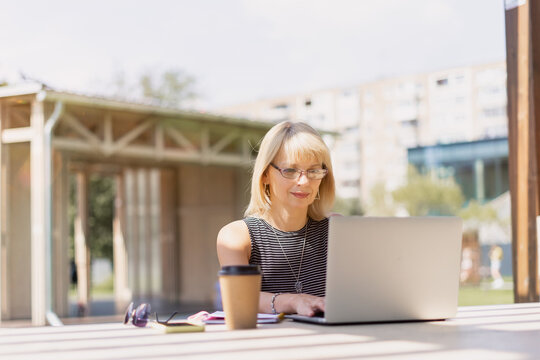 Adult Woman in glasses having video call with laptop outside in park. Happy and smiling senior working and drinking coffee. Using computer. Distance learning online education and online shops.