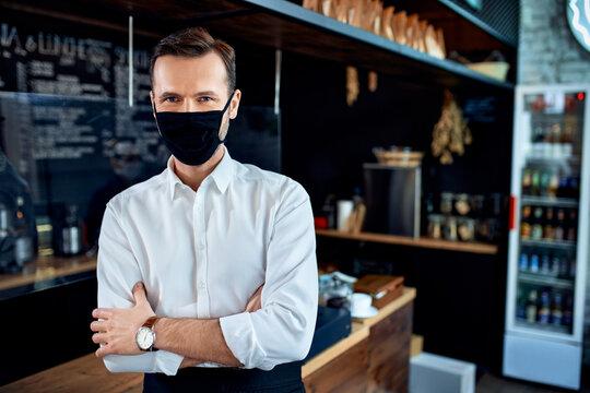 Portrait of barista restaurant owner wearing mask standing in cafe