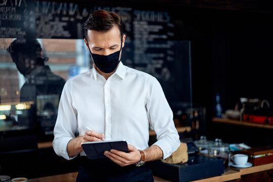 Portrait of restaurant cafe owner using digital tablet